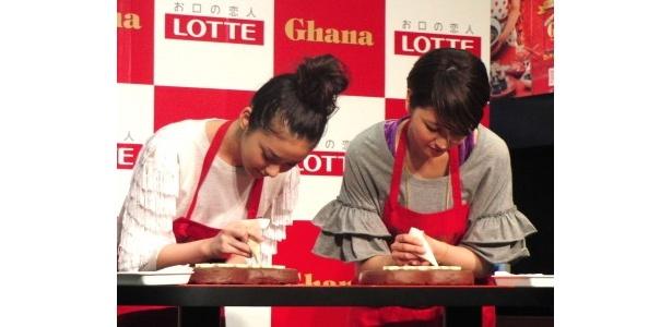 ハート型のチョコに応援メッセージを書く長澤と武井