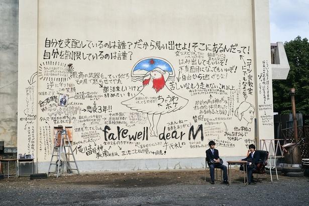 物語の鍵を握る校舎裏の落書きを背に佐藤と高橋の2人が座る場面写真も到着