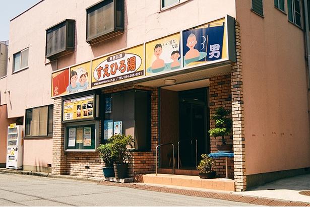 【写真を見る】川崎大師 平間寺そばのごりやく通り沿い。正式な屋号は「寿恵弘湯」だが、「読めないお客さんが多い」(店主)ため、看板は「すえひろ湯」に