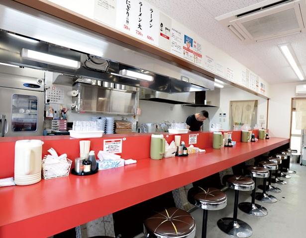 南京ラーメン 黒門 / 厨房内も美しく磨かれた、清潔感のある店内。卓上には胡椒とニンニク醤油を備える