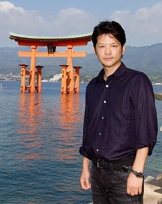 水上に浮かぶ厳島神社を前に立つ緒形直人