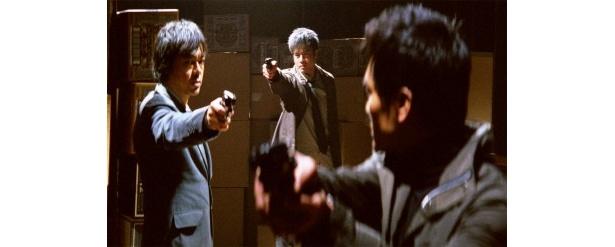 【写真をもっと見る】銃口を突きつけ合う3人。衝撃の展開に息を飲む