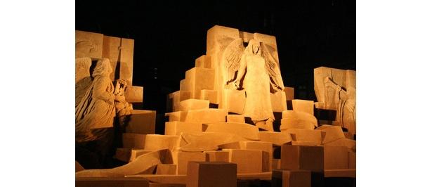 砂で作られた彫刻が光に照らされ、さらに美しさを増しています