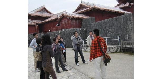 """広い上に一部復旧されていない首里城について、時に図面を用いて説明する""""テンペスト公認ガイド""""の声にツアー参加者は熱心に耳を傾けていました"""