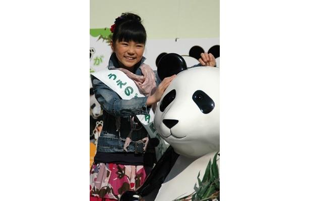 「うえのパンダ歓迎大使」に任命された大橋のぞみちゃん。ジャイアントパンダ保護のための募金箱におこずかいの一部を寄付してニッコリ