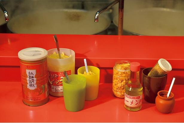 【写真を見る】卓上には、生姜、ニンニク、ゴマなど味変の調味料がずらりとそろう。