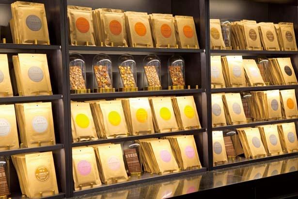 【写真を見る】棚にはカカオの産地の個性をそのまま味わえるタブレットが30種以上並ぶ/ル・ショコラ・アラン・デュカス 大丸心斎橋