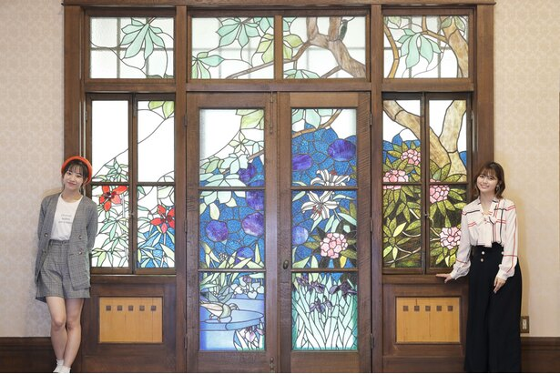 【写真を見る】1階大広間にある大きなステンドグラスに感激する北野瑠華と日高優月