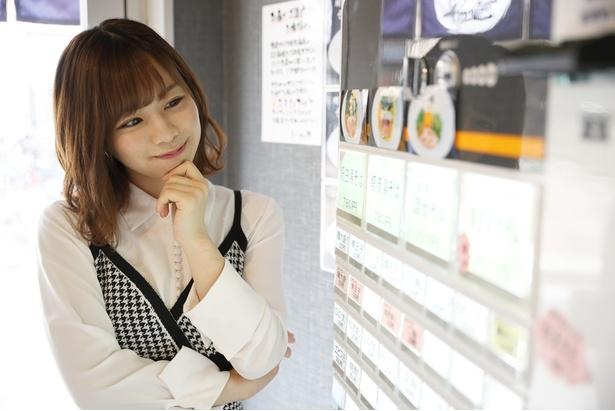 【写真を見る】券売機を笑顔で眺める、おしりんこと青木詩織