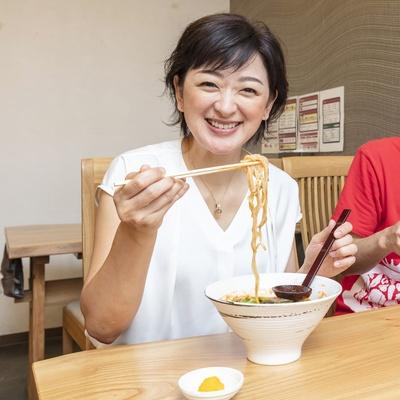 「トマト麺Mami」を試食中。佐藤麻美さんも「おいしい!」と思わず笑顔