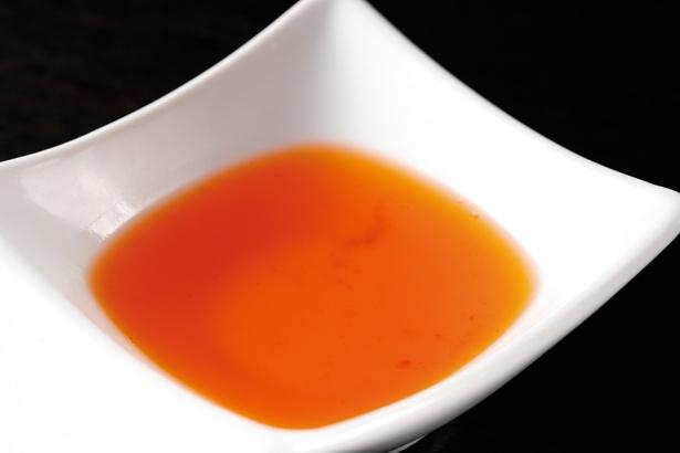 仕上げに使用する自家製の甘エビ油は、透明感のある鮮やかな緋色 / えびそば 緋彩