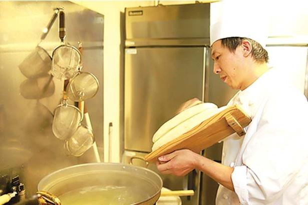 チャイナワン / 修業を積んだシェフが麺生地を大胆にカットしていく