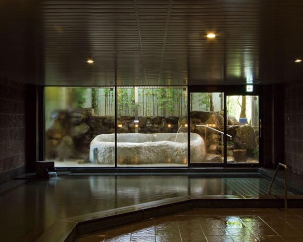 大浴場は、約8tもの一枚岩をくり抜いて作った露天風呂を備える / 旅館 吉田屋