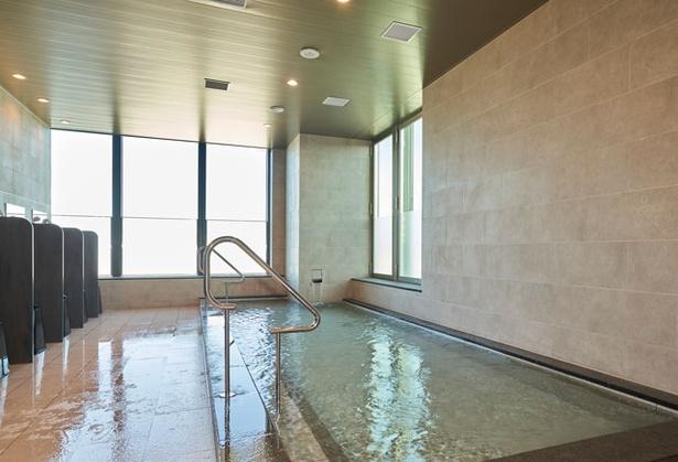 【写真を見る】都ホテル 博多 / 男女別の内湯(写真は女湯)。男湯にはドライサウナ、女湯にはスチームサウナがある プールサイドのソファで、優雅なひと時を