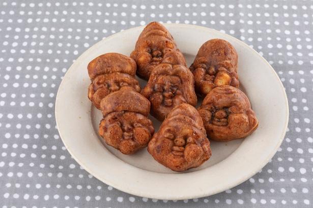 """「人形焼」1個120円(税込)。あんこは十勝産の小豆を使用。顔をよく見ると、毘沙門天が不在の""""六福神""""。これは焼き型が1セット6個のためで不運にも毘沙門天が外された"""