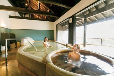 地下300mと30mから湧く2つの湯を2つの浴槽で楽しめる大浴場。ぬる湯の方は体に炭酸の泡が付着する / 万象の湯