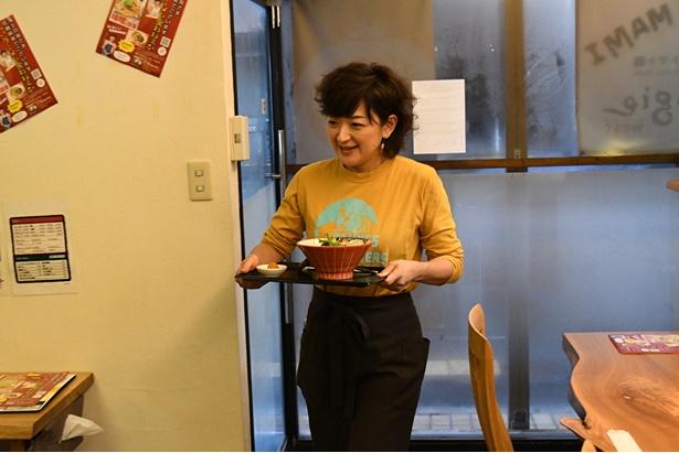「トマト麺Mami」をお客さんの元へと運ぶ佐藤さん
