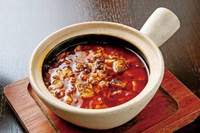 エッセンス チャイ ニーズ キッチン / 「麻婆豆腐」(600円)。土鍋でアツアツ状態をキープ。赤&黒の豆板醤と山椒がピリッと刺激的