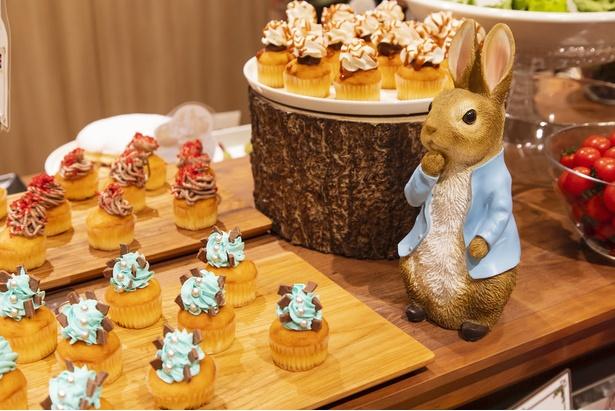 「ピーターラビット(TM)のブルージャケットカップケーキ」(写真手前)や「チョコベリーカップケーキ」(同奥)などが並ぶブッフェ台にはピーターも