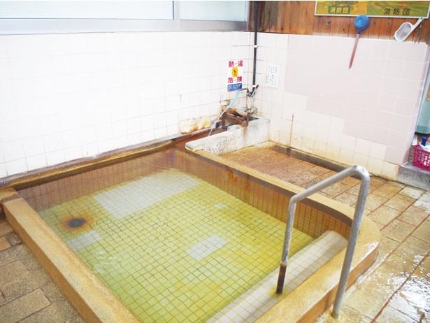 向かいの「まさ食堂」で100円を支払い、入浴札を受け取ったら、浴室の札かけにかけて入浴を / 上人湯
