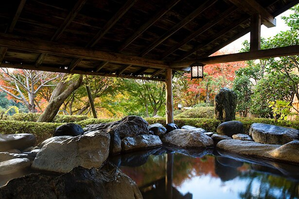 屋根を配した長寿の湯。庭園の先には美しい紅葉が