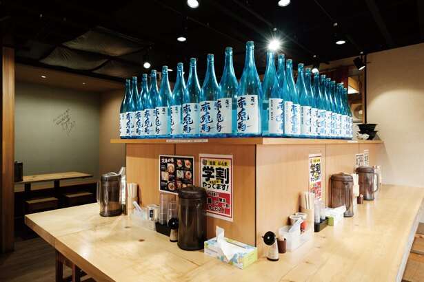 お酒の瓶が並び立つカウンターは、何とも印象的!/ 麺屋ぶんま