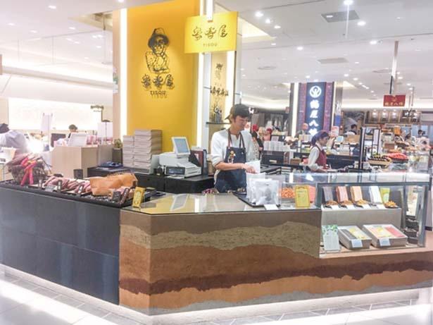 販売台の壁面には店名の由来でもある地層のデザインが施されている/蜜香屋 TUTITO