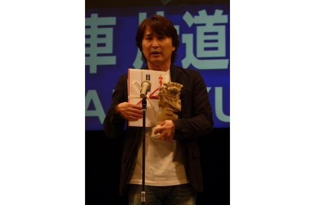 「海人賞(Peace部門)」を受賞し、副賞であるシーサーを手に喜びを語る重松プロデューサー