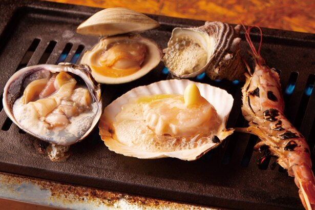 浜焼きで味わえる食材は、大アサリ、天然車エビ、ホタテ、サザエ、スルメイカ、カキなど常時10種類 / 鮮魚浜焼きセンター なご八 日比野店