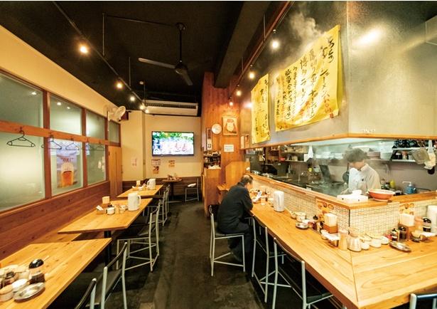 めんくいや 博多駅東店 / 木目調のカウンターとテーブル。持ち帰り用の麺、モツ鍋も販売