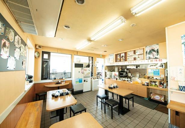 長浜ラーメン めんめん / オープンキッチンで作っている様子が見られる。無料の高菜を置く