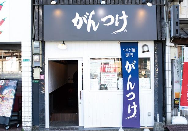つけ麺専門 がんつけ / 西鉄二日市駅の西口が至近。白壁に青い看板とのぼりが映える