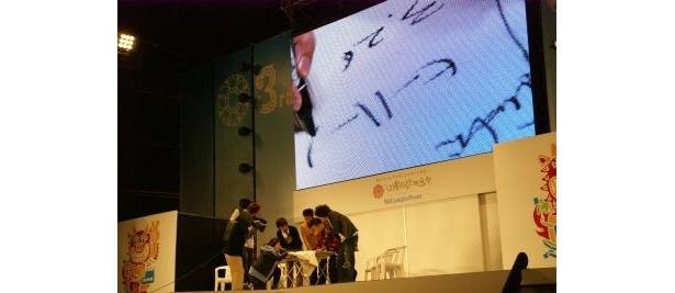 私物にサインとギャグをその場で書き込む小杉