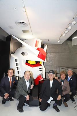 『機動戦士ガンダム』のフェイスモニュメントの前で笑顔を見せる、古谷徹(右から2人目)ら