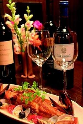 「お箸Dining Bonappetit~ぼなぺっち~」の「新鮮魚介のアクアパッツァ」(2520円~)、イタリア産がメインのボトルワイン(3570円)とともに