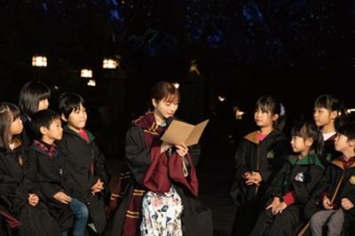 【写真を見る】子供たちにショーの物語を読み聞かせる石原さん/ユニバーサル・スタジオ・ジャパン「ホグワーツ・マジカル・ナイト~ウィンター・マジック~」