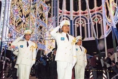 白服の3人を先頭に、うしろまで警備員が並ぶ儀礼隊。周囲には被災された方も多く集まり、特別な雰囲気に/神戸ルミナリエ