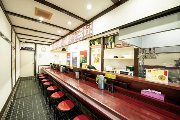 店内はカウンターのみ。宮崎各地の観光ポスターが壁に貼られる / 宮崎辛麺屋 辛福 西新店