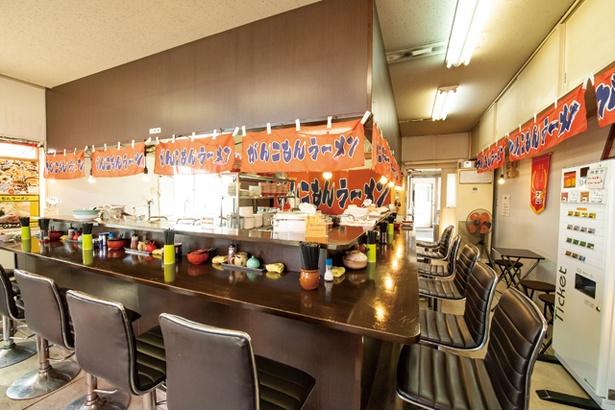 カウンターが厨房を囲む。24時間、ラーメンを楽しめるのが魅力 / がんこもんラーメン 福岡店