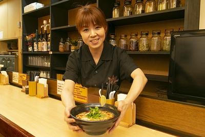 店長の綱島綾子さん。「辛くないスパイスラーメンです。辛いのがお好みの方には「辛さ増し」(+30円)もあります。1辛から5辛まで選べます」