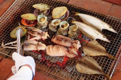 地元産の魚介類を、目の前にある炭火で焼き上げてくれる。焼きたては旨さも格別! / 海女小屋体験施設 さとうみ庵