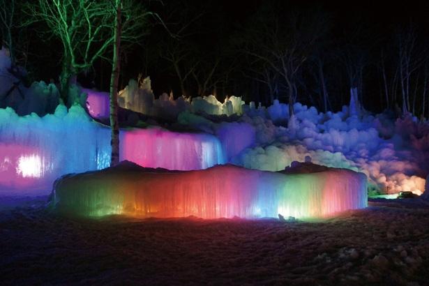 【写真を見る】日が落ちると赤、青、緑にライトアップされ、幻想的な雰囲気に。白い氷と青空のコントラストが美しい、昼間の観賞もオススメ / 氷点下の森