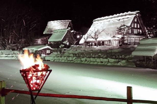 藁葺(わらぶ)き屋根や木々に積もった雪が、色とりどりのライトに照らされる。周囲が暗いので、集落が浮かび上がって見える / 飛騨の里