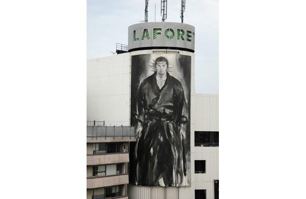 「ラフォーレ原宿」に登場した、縦18.2m、横10.2mの巨大武蔵。「この国には、底力がある」という熱いメッセージは、震災の危機を乗り越えようとする今の状況とシンクロする