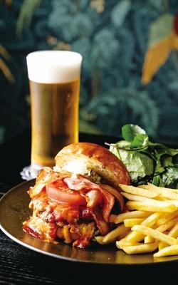 【写真を見る】Leonard / 人気No.1は、ビーフパティにチェダーチーズやベーコンなどをはさむ「レオナルドバーガー」(昼・夜1100円)。ランチはポテトとサラダ付き(写真)
