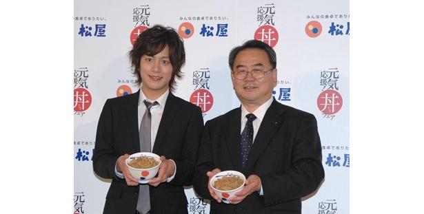 松屋フーズ・代表取締役社長の緑川源治さんと牛めしを持って並ぶ溝端さん