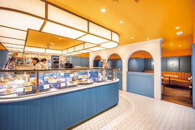 ブランドカラーのイエローでまとめられ、明るい雰囲気の店内。併設のカフェはテーブル席のみ/クレーム デ ラ クレーム