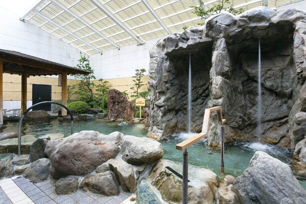 岩造りが特徴的な和風の露天風呂。洞窟の打たせ湯は強めの水圧で疲れもスッキリとれそう / くつろぎ天然温泉 津島 湯楽