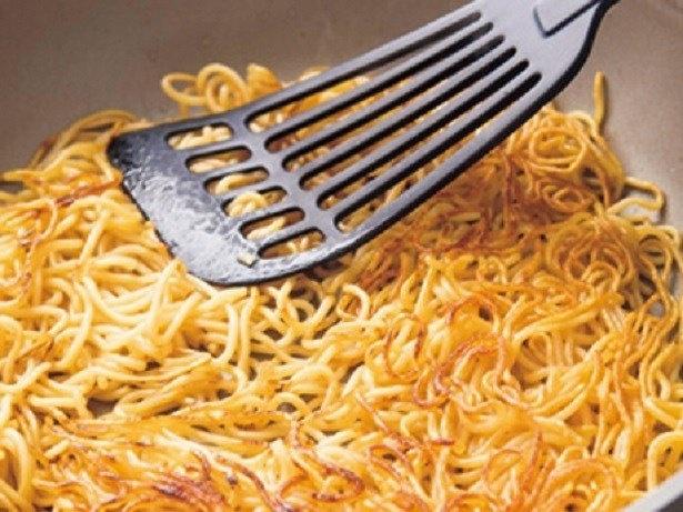 フライパンに麺を広げ、へらで押さえながらこんがり焼きつける