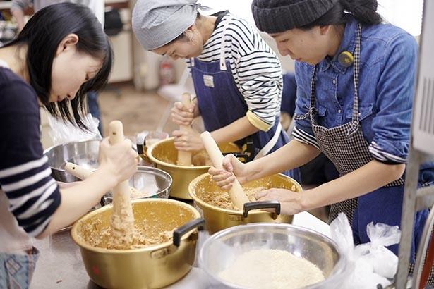 【写真】真剣に味噌作りを行う参加者たち